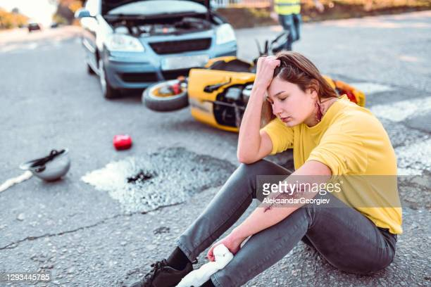 female still in shock after getting hit by car with motorcycle - crash stock pictures, royalty-free photos & images