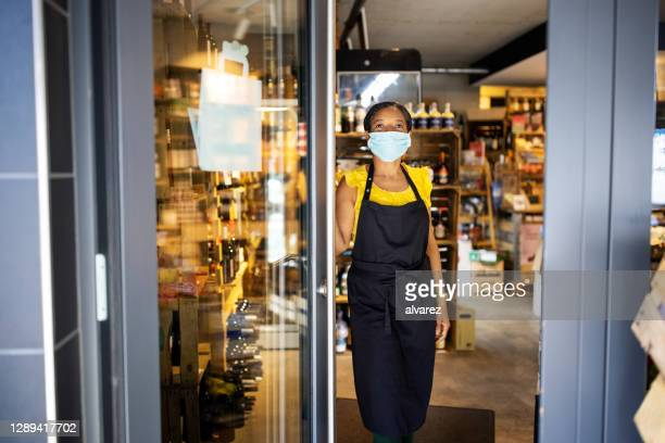 female store owner at doorway during covid-19 - opening event stock pictures, royalty-free photos & images