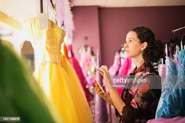 Female Store Owner Examining Gowns