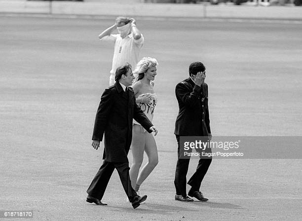 A female streaker is escorted from the ground by police officers during the 1st Test match between England and India at Lord's Cricket Ground London...