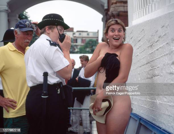 Female streaker tries to cover up as she is escorted from the ground by a policewoman during the 1st Test match between England and Pakistan at...