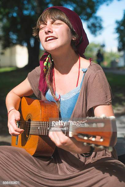 female street musician playing guitar - busker stock pictures, royalty-free photos & images