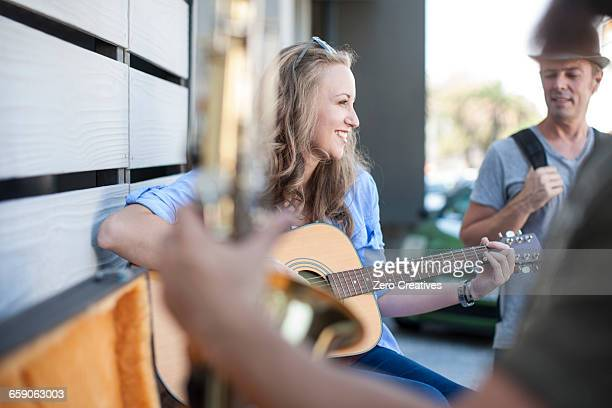female street musician, playing guitar - busker stock pictures, royalty-free photos & images