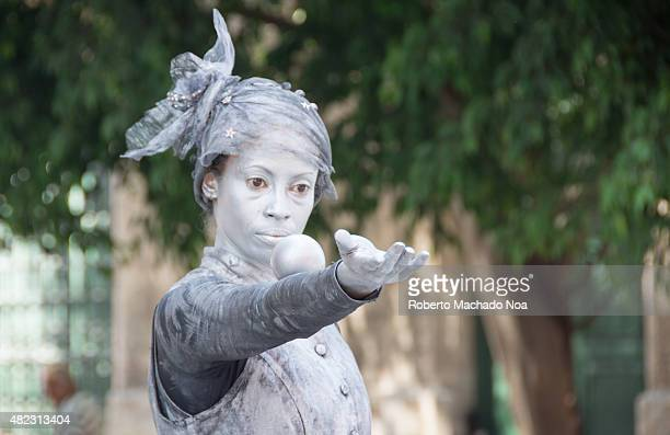 Female street performer busking as a living statue She Is dressed in silver with silver body paint and a silver hat doing a trick with a silver ball...