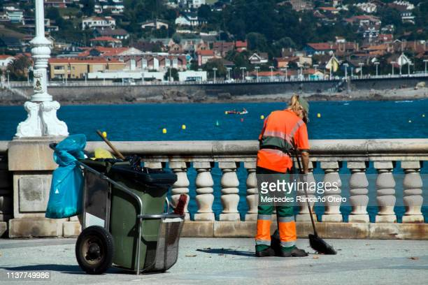 female street sweeper with cart, broom and dustpan in san lorenzo beach in gijón, spain.. - street sweeper stock pictures, royalty-free photos & images