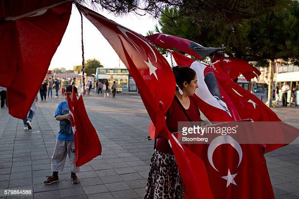 A female street vendor sells Turkish national flags on a square in Istanbul Turkey on Saturday July 23 2016 Aiming to limit the economic fallout from...