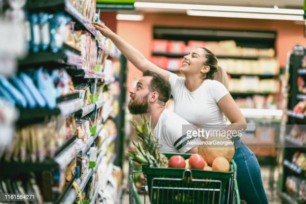 female stretching above boyfriend to buy groceries - market retail space stock pictures, royalty-free photos & images