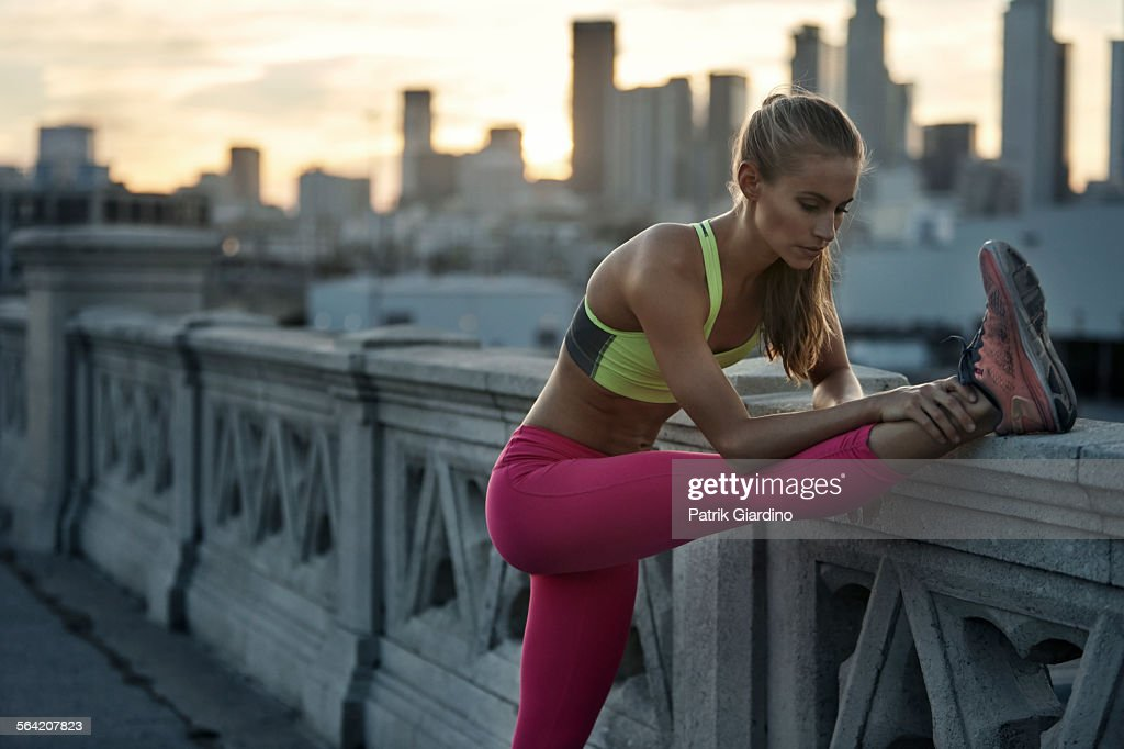 Female stretching hamstrings before run : Stock Photo