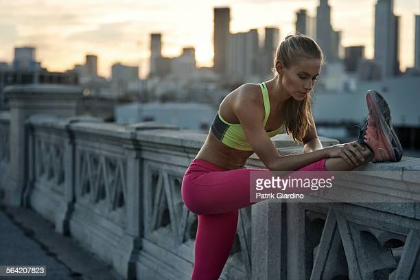 female stretching hamstrings before run - sportswear stock pictures, royalty-free photos & images