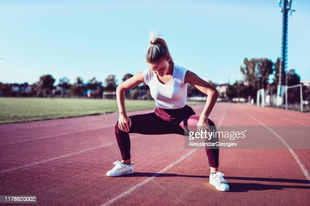 female stretching legs before running - legs apart stock pictures, royalty-free photos & images