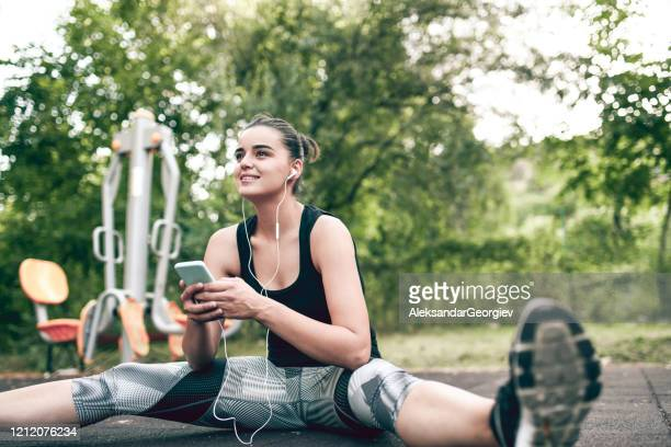 female stretching with music on smartphone in park - colors soundtrack stock pictures, royalty-free photos & images