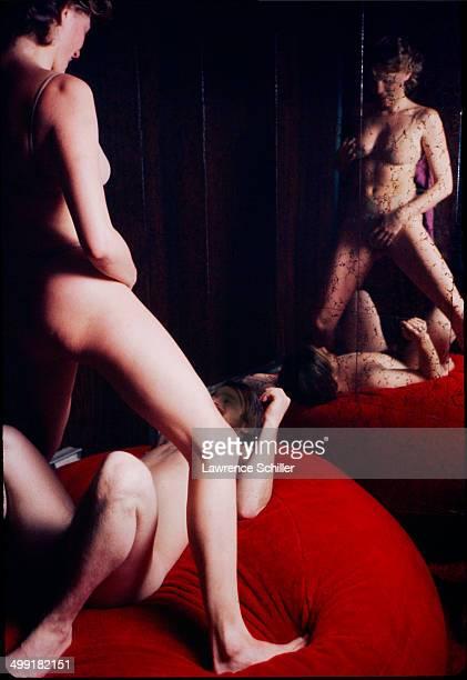 A female stripper performs for a male client who lies back on a cushion San Francisco California 1976