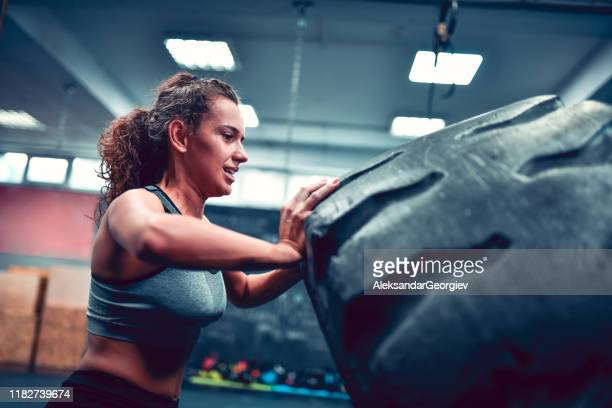 female struggling with tire pushing exercise in gym - struggle stock pictures, royalty-free photos & images