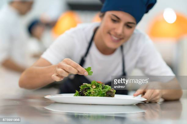 Female student at a gourmet institute finishing the details of a salad she just made