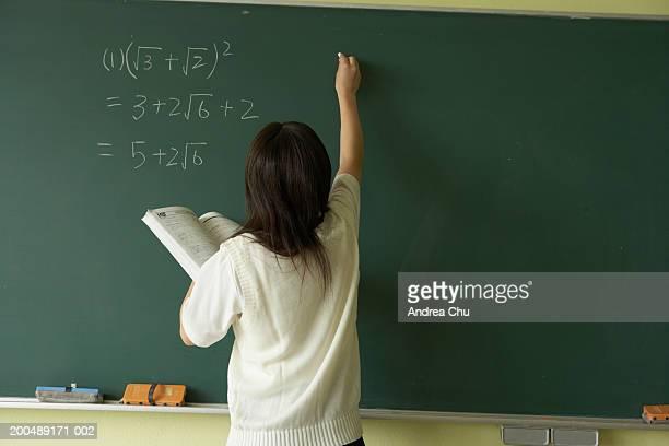 Female student (14-16) at blackboard doing mathematics, rear view
