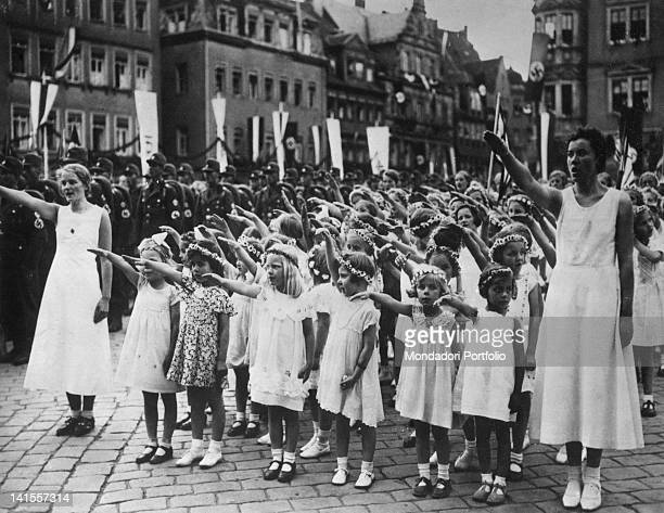 A female student body making the Nazi salute during a military parade of the SA of the Nazi Party