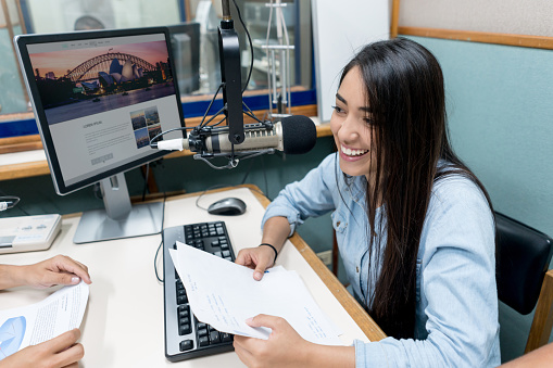 Female student broadcasting from the university's radio station 669775772