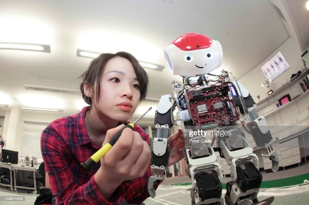 female student building robot : Stock Photo