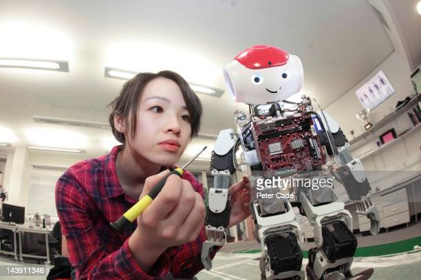 female student building robot - leanincollection stock pictures, royalty-free photos & images