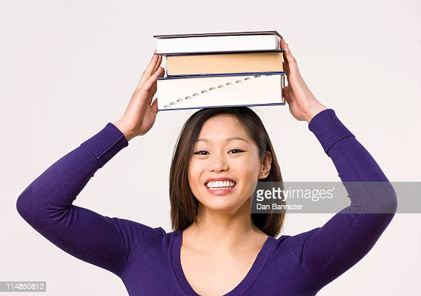 Female student carrying book on head