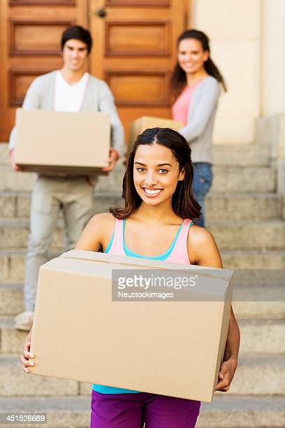 Female Student Carrying Cardboard Boxes With Friends In Background
