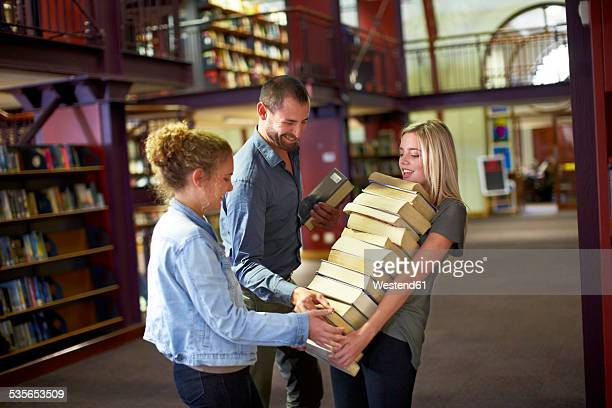 Female student carrying pile of books in a library assisted by friends