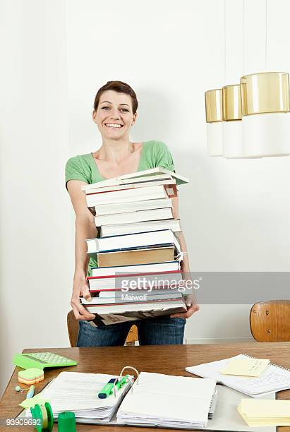 Female student carrying stack of books
