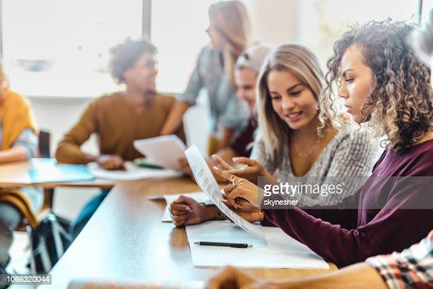 female student cooperating with her friend while studying in classroom. - studentessa foto e immagini stock