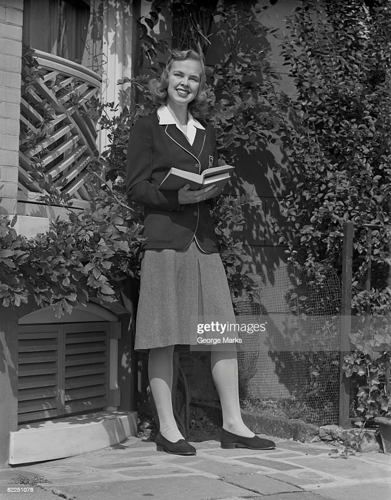 Female student holding book in back yard, portrait : Stock Photo