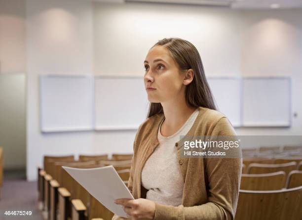 female student holding essay in lecture hall - tensed idaho stock photos and pictures