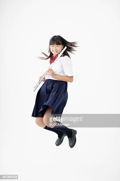 Female student holding flute jumping, studio shot