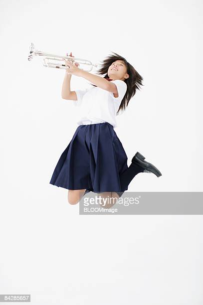 Female student holding trumpet jumping, studio shot