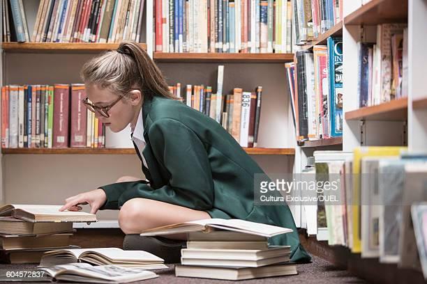 Female student in library with open books, studying