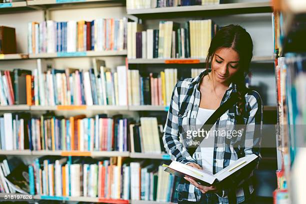 Female student in the library reading book.