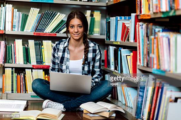 Female student in the library using laptop