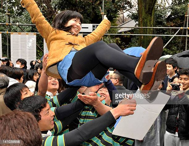 A female student is tossed into the air in a celebration after passing the entrance examination for a prestigious Tokyo University in Tokyo on March...