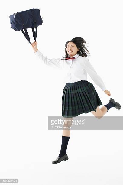 Female student jumping, holding bag, studio shot