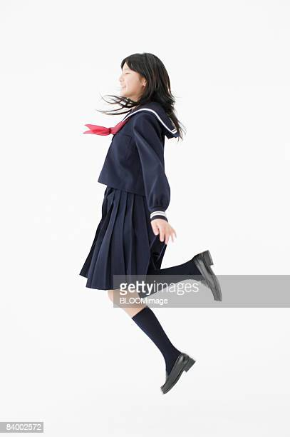 Female student jumping, side view, studio shot