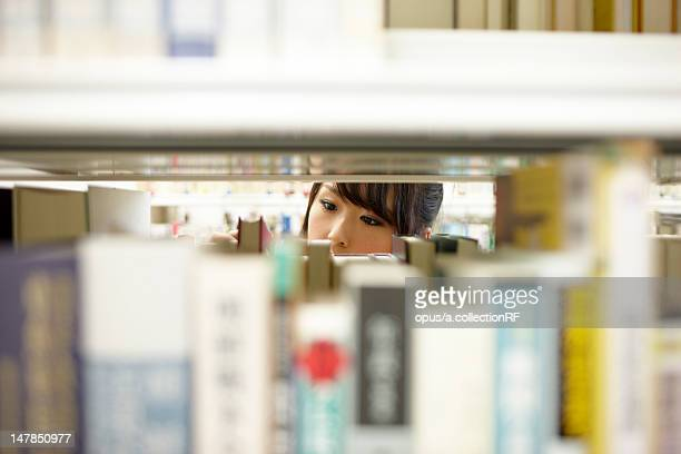 Female student looking for book in library