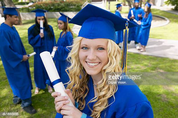 female student on graduation day and students in the background - graduation background stock pictures, royalty-free photos & images
