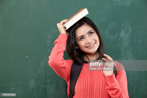 female student placing book on head while standing by blackboard - putting stock pictures, royalty-free photos & images