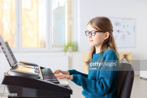 studentinnen spielen klavier in der musikklasse - izusek stock-fotos und bilder