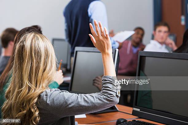 Female student raises hand in classroom