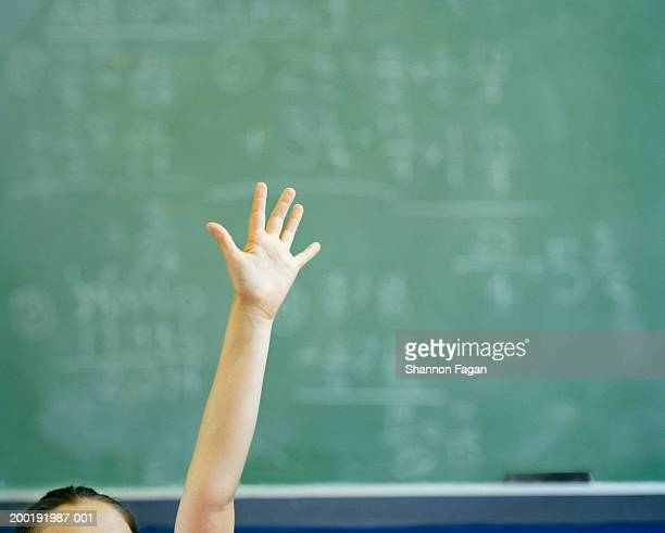 female student (12-14) raising hand in classroom, close-up - education stock pictures, royalty-free photos & images