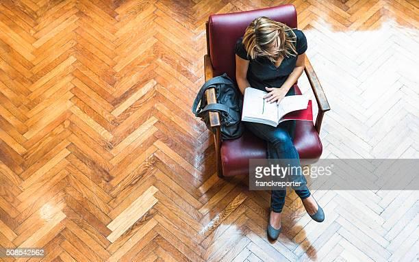 Estudiante mujer leyendo un libro biblioteca