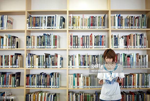 Female student reading book at library
