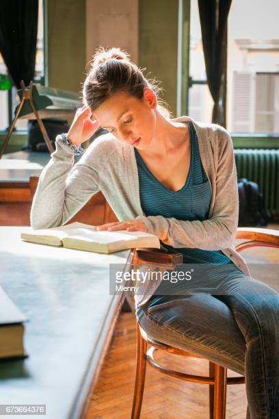 Female student reading book in university library