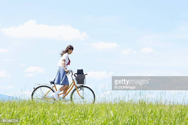 Female student riding bicycle in green field
