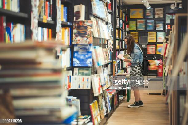 female student searching for books in the book store (book covers are edited) - textbook stock pictures, royalty-free photos & images