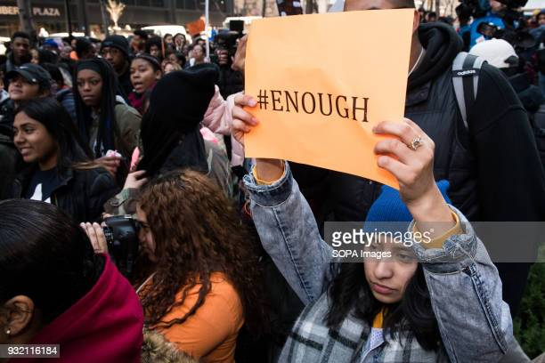 A female student seen holding a placard which reads 'ENOUGH' during the National School Walkout a 17 minute walkout by students in honor of the 17...